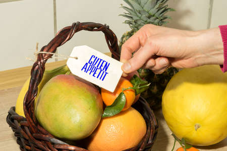 A basket of fresh fruits and a sign with the word Bon appetit Archivio Fotografico