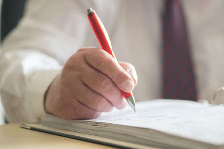 A man with a pen signs a document Stock Photo