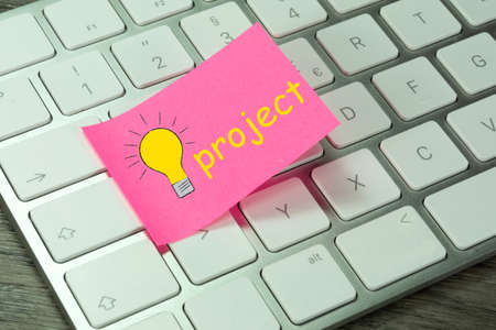 A computer and note with lightbulb and the word Project