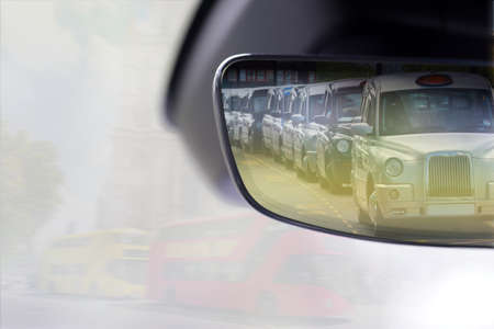 Taxis of London in the rearview mirror of a car