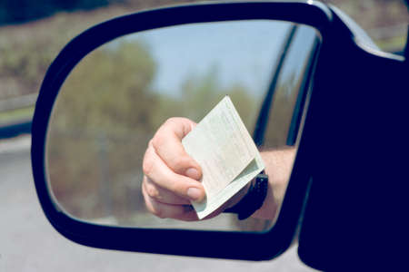 A man shows his vehicle registration at a check