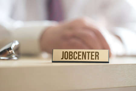 A man and a sign with the imprint Jobcenter Stock Photo