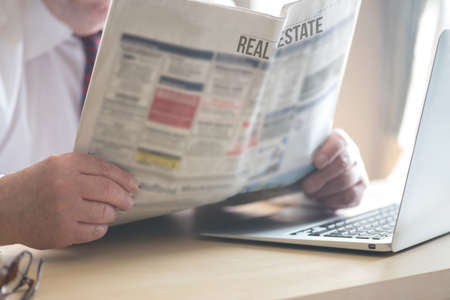 A man and a newspaper Real Estate