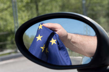 Exterior mirror of the car and a man holding the flag of the EU in hand