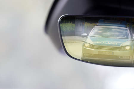 Interior of a vehicle and police car in the rearview mirror