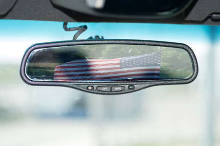 The flag of USA in the interior mirror of a car