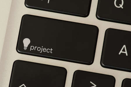 A computer and a button with lightbulb and the word Project