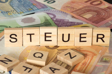 Euro bills and wooden letters with the word TAX