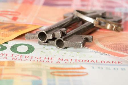 Banknoten Schweizer Franken und Schlüssel für eine Wohnung