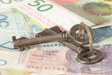A key, and banknotes Polish zloty and Swiss francs Stock Photo