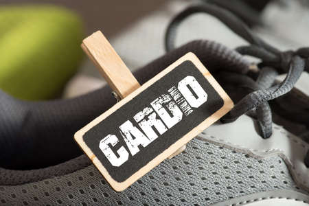 Running shoes and a sign with the word cardio Stockfoto