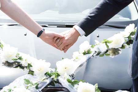 A bridal couple is standing in front of wedding sedan