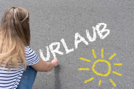A woman paints the sun and the word vacation on the street