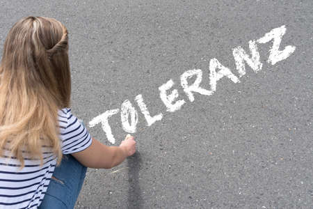 A young woman writes the word tolerance on the street Фото со стока