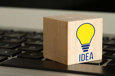 A computer and idea with lightbulb