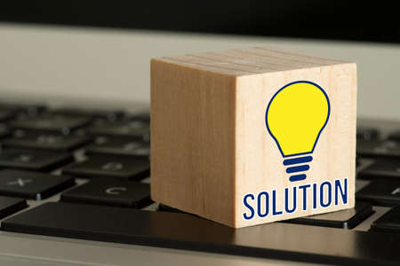 A computer, lightbulb and the word solution
