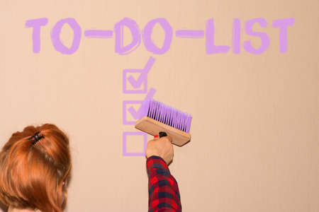 A woman paints a to-do list on a wall