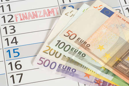 Euro banknotes, calendar and date at the tax office