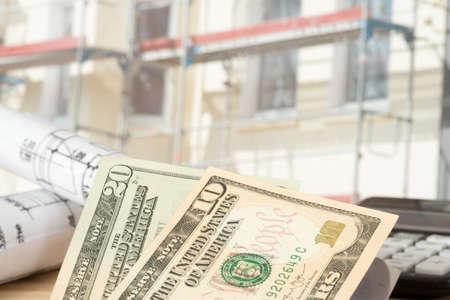 Dollargeld, Blaupausen und Baustelle für ein Haus