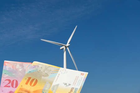 Wind turbine in Switzerland and banknotes Swiss francs Stock Photo
