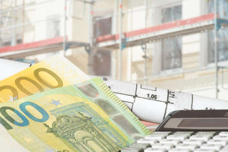 Construction site, euro bills and blueprints