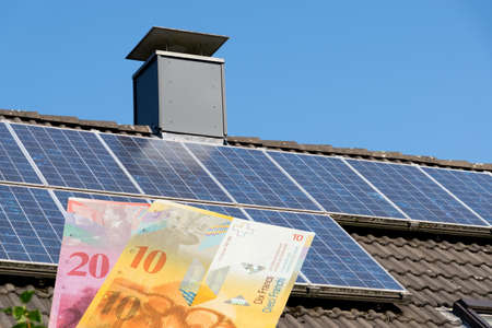 A house with solar system and money Swiss francs