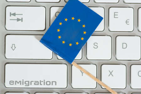 A computer, European Union flag and immigration