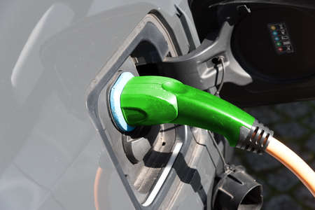 An electric car is charged with energy at a charging station Stock fotó