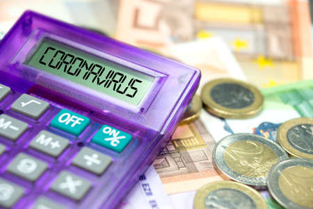 Calculators, euro banknotes and corona virus impact on financial status in Europe