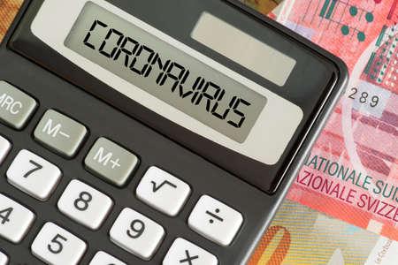 Swiss franc banknotes, calculator and corona virus in Switzerland