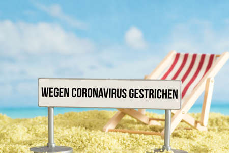 A beach, sun lounger and note vacation canceled due to corona virus