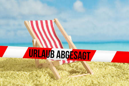 Beach, sun lounger and barrier tape with the message Vacation Canceled