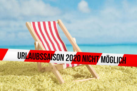 Beach, sun lounger and barrier tape with the note holiday season 2020 not possible