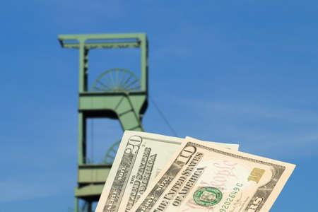 Mine tower, mine and dollar banknotes