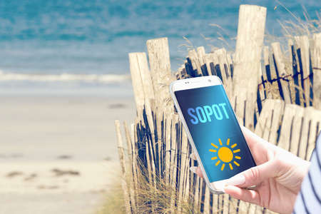 Beach, smartphone and vacation in Sopot Poland