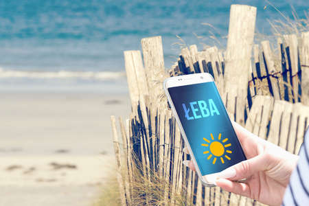 Beach, smartphone and vacation in Leba Poland