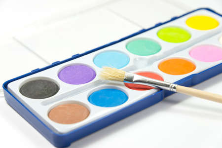 Paints in the paint box and a brush Imagens