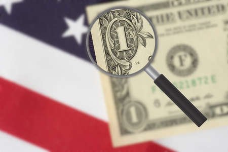 Flag of USA, dollar bank note and a magnifying glass