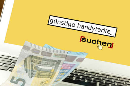 Euro banknotes, computers and search for cheap cell phone tariffs Standard-Bild