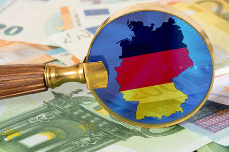 Euro banknotes and flag of Germany in a magnifying glass