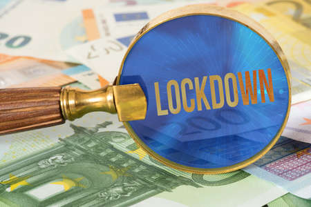 Euro banknotes, magnifying glass and lockdown