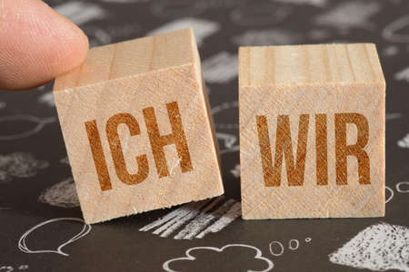 Two dice with the words I and We Standard-Bild