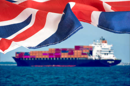A container ship and flag of Great Britain Standard-Bild