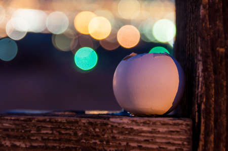 humpty dumpty: Broken Egg crying out his yolk over city lights Stock Photo