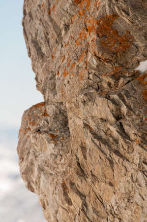 face covered: A rough textured rock face covered in orange Stock Photo
