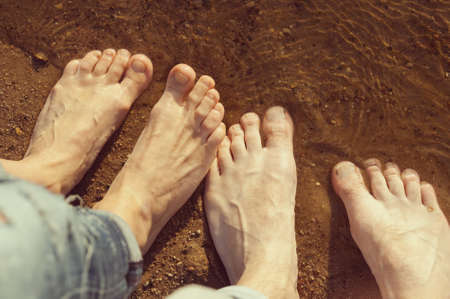 shoeless: womans and mans feet standing on the sand