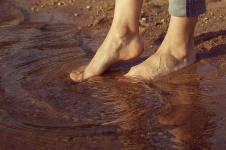 shoeless: womans feet standing in the water on the sand
