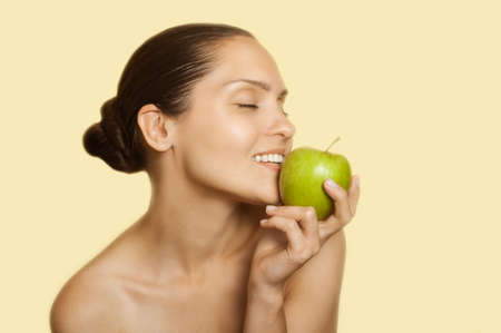 care about the health: adult girl pressed her lips to the green apple