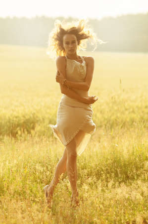 summer dress: jumping girl in a dress on  summer meadow