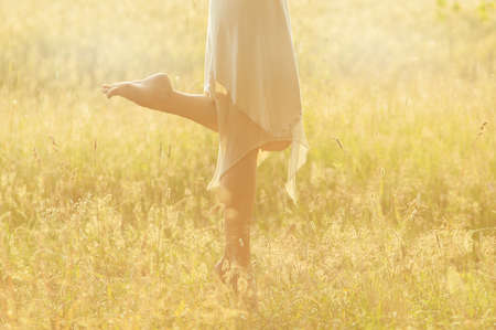 summer dress: girls feet in a dress on a summer meadow Stock Photo